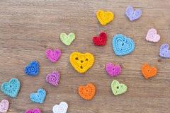 Muchos corazones multicolores del ganchillo en el fondo de madera para el día de tarjetas del día de San Valentín Fotografía de archivo libre de regalías