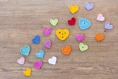 Muchos corazones multicolores del ganchillo en el fondo de madera para el día de tarjetas del día de San Valentín Imagen de archivo libre de regalías