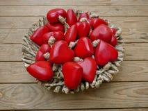 Muchos corazones rojos en una cesta delante de una pared marrón del tablón Foto de archivo