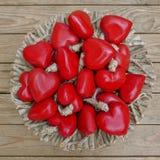 Muchos corazones rojos en una cesta delante de una pared marrón del tablón Fotos de archivo libres de regalías