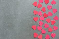 Muchos corazones rojos y rosados en un fondo concreto gris Día del `s de la tarjeta del día de San Valentín Fotos de archivo