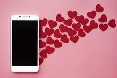 Muchos corazones y smartphone Concepto a tener gusto en redes o el app sociales el fechar Fondo rosado foto de archivo libre de regalías