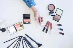 Muchos cosméticos del maquillaje diferentes en el fondo de madera blanco de la tabla Imagenes de archivo
