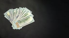 Muchos dólares giran contra un contexto negro Lugar bajo título 4k almacen de video