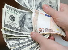 Muchos dólares que caen en la mano del hombre con el dinero, aislado Fotografía de archivo