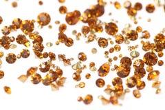 Muchos diamantes artificiales dispersados En un fondo blanco Fotos de archivo libres de regalías
