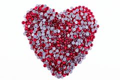 Muchos diamantes artificiales rojos hechos en la forma de un corazón en un fondo blanco Visión superior Imagen de archivo libre de regalías