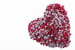 Muchos diamantes artificiales rojos hechos en la forma de un corazón en un fondo blanco Visión superior Imágenes de archivo libres de regalías