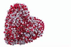 Muchos diamantes artificiales rojos hechos en la forma de un corazón en un fondo blanco Visión superior Fotografía de archivo libre de regalías