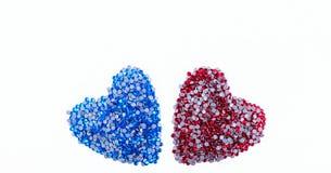 Muchos diamantes artificiales rojos y azules hechos en la forma de un corazón en un fondo blanco Visión superior Fotos de archivo