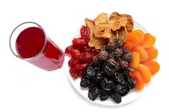 Muchos diversos albaricoques secados secados de las frutas, manzanas, peras, pasas en una placa blanca y un vidrio de compota Foto de archivo libre de regalías