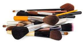 Muchos diversos cepillos cosméticos del maquillaje en blanco imagenes de archivo