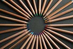 Muchos diversos lápices coloreados en fondo negro Imagen de archivo