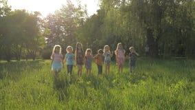 Muchos diversos niños que corren en el parque en día de verano soleado en ropa casual almacen de metraje de vídeo