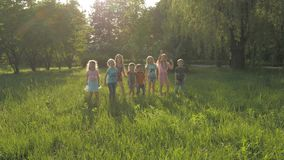 Muchos diversos ni?os que corren en el parque en d?a de verano soleado en ropa casual almacen de metraje de vídeo