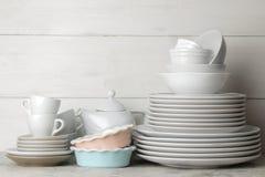Muchos diversos platos dinnerware en un fondo del cemento ligero platos para servir la tabla diversos placas, cuencos, y Cu fotos de archivo