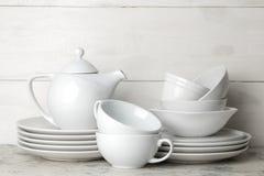 Muchos diversos platos dinnerware en un fondo del cemento ligero platos para servir la tabla diversos placas, cuencos, y Cu fotografía de archivo libre de regalías