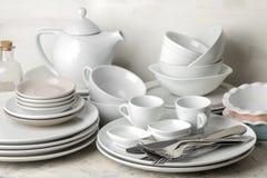 Muchos diversos platos dinnerware en un fondo del cemento ligero platos para servir la tabla diversos placas, cuencos, y Cu foto de archivo libre de regalías