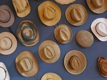 Muchos diversos sombreros de paja en una pared azul Foto de archivo