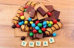 Muchos dulces con el azúcar de la palabra en la superficie de madera, comida malsana Fotografía de archivo libre de regalías