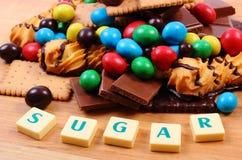 Muchos dulces con el azúcar de la palabra en la superficie de madera, comida malsana Imagen de archivo