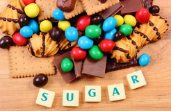 Muchos dulces con el azúcar de la palabra en la superficie de madera, comida malsana Imagenes de archivo