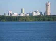 Muchos edificios de la ciudad después del río y del bosque Fotos de archivo