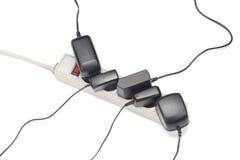 Muchos enchufes enchufaron el cable de extensión aislado en blanco Imágenes de archivo libres de regalías