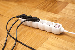 Muchos enchufes taparon en multitoma eléctrico en piso Foto de archivo libre de regalías