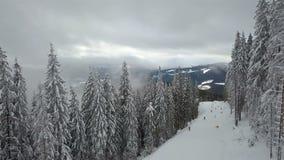 Muchos esquiadores y snowboarders descienden abajo de la cuesta del esquí almacen de metraje de vídeo