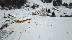 Muchos esquiadores y snowboarders descienden abajo de la cuesta del esquí metrajes