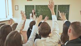 Muchos estudiantes que aumentan sus manos en la clase para una respuesta Escuela rusa almacen de metraje de vídeo
