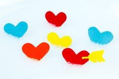 Muchos formas coloreadas de papel del corazón en nieve Imagenes de archivo