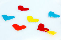 Muchos formas coloreadas de papel del corazón en nieve Fotos de archivo