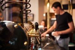 Muchos golpecitos de oro de la cerveza en la barra Imagen de archivo libre de regalías