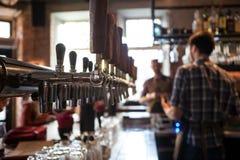 Muchos golpecitos de oro de la cerveza en la barra Fotos de archivo