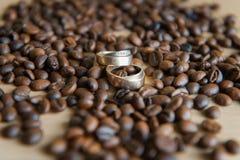 Muchos granos de café marrones con los anillos de bodas Fotografía de archivo libre de regalías