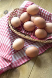 Muchos huevos crudos marrones están en una cesta de mimbre en la tabla Foto de archivo