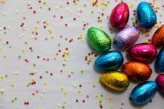 Muchos huevos de Pascua coloreados derechos del chocolate en el fondo blanco y el confeti colorido imagen de archivo