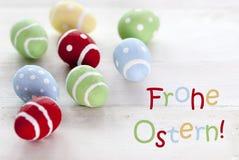 Muchos huevos de Pascua coloridos con el texto alemán Frohe Ostern significan Pascua feliz Imagen de archivo libre de regalías
