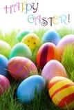 Muchos huevos de Pascua coloridos en hierba verde con el texto Pascua feliz Foto de archivo