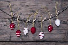 Muchos huevos de Pascua rojos y blancos que cuelgan en línea Foto de archivo