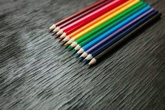 Muchos lápices coloreados en un fondo negro Nuevos lápices Foto de archivo