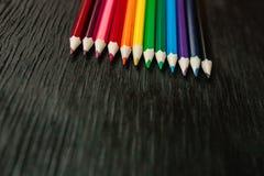 Muchos lápices coloreados en un fondo negro Nuevos lápices Fotos de archivo libres de regalías