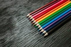 Muchos lápices coloreados en un fondo negro Nuevos lápices Foto de archivo libre de regalías
