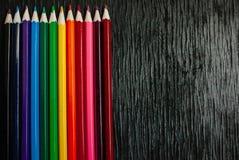 Muchos lápices coloreados en un fondo negro Nuevos lápices Imagen de archivo libre de regalías