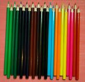 Muchos lápices coloreados en un fondo rosado Foto de archivo