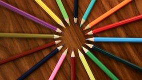 Muchos lápices multicolores giran en un círculo en un fondo de madera negro Oficina o escuela, día del conocimiento, el primer de metrajes