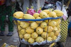 Muchos mangos amarillos jugosos maduros en una cesta se venden en un str imagenes de archivo