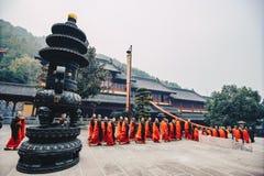 Muchos monjes en trajes rojos que caminan en Lufeng Temple fotografía de archivo